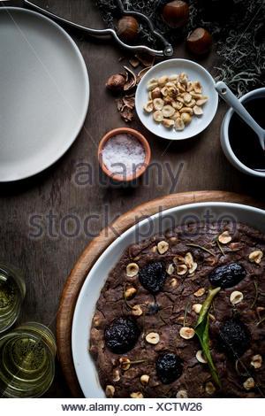 Festliche Mittelmeer Kastanien Mehl Kuchen in weiße Schale auf Set Holztisch mit Zutaten, Weihnachtsdekoration und Wein gla - Stockfoto