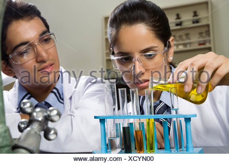 Mädchen, die eine Flüssigkeit in ein Reagenzglas gießen