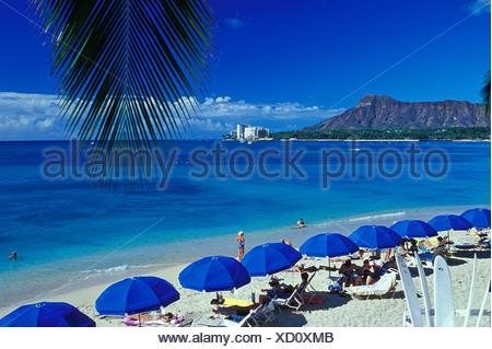 Urlauber genießen eine Aussicht auf Diamond Head Krater, wie sie am einladenden Sandstrand von Waikiki Beach.This Foto entspannen aus der - Stockfoto