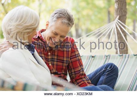 Gerne älteres paar sitzen in Hängematte im Park im Herbst - Stockfoto