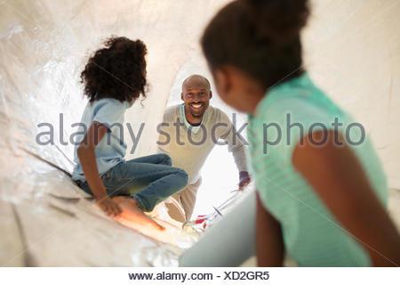 Lächelnde Vater und Töchter spielen im Science center - Stockfoto