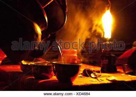 Heißes Wasser bekommt in Tassen aus einem Kessel, um Tee als Gas ...
