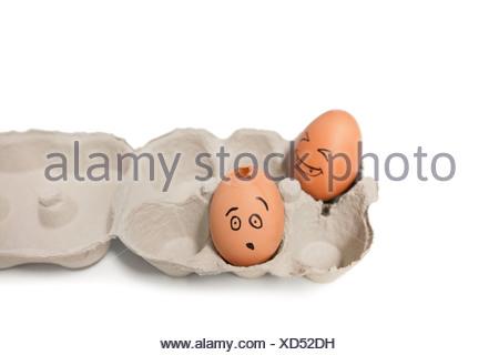 Karton von braunen Eiern mit einem gerissenen Ei - Stockfoto
