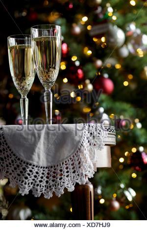 Champagnergläser auf einen Tisch, mit einem Weihnachtsbaum hinter - Stockfoto