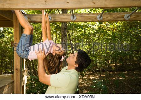 Klettergerüst Zum Aufhängen : Zwei kinder hängen vom klettergerüst auf einem spielplatz