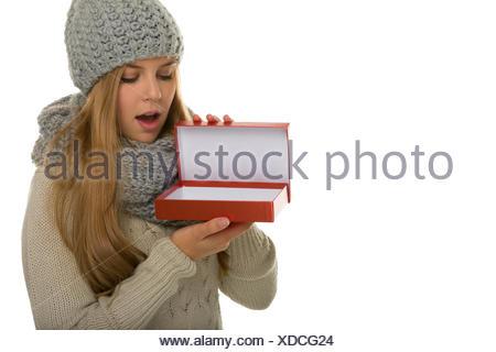 Junge Frau / Mädchen Trägt Strickware Und Schaut heute in Eine Geschenkverpackung. Wie Eine Überraschung Zu Fernsehsendern Oder Ein meistverkauftes Im Neuen Jahr. Inhalt Kann Selbst Hinzugefügt werden - Stockfoto