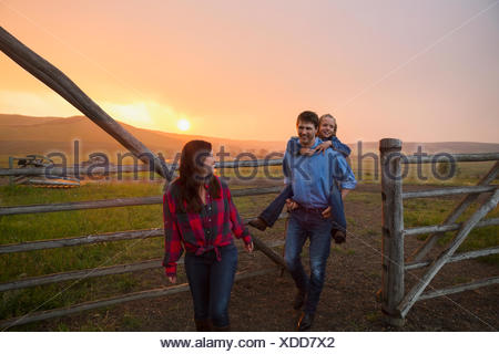 Familie gehen durch Weide Tor bei Sonnenuntergang - Stockfoto