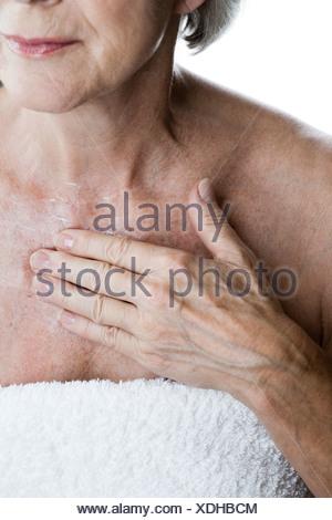 Eine ältere Frau anwenden Feuchtigkeitscreme auf ihrer Brust - Stockfoto