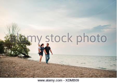 Schwangere paar Strand entlang schlendern mit männlichen Toddlersohn, Lake Ontario, Kanada - Stockfoto
