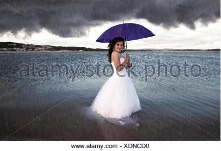 Braut am Strand im Regen, Portugal - Stockfoto