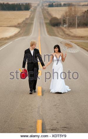 drei Hügel, Alberta, Kanada; eine Braut und Bräutigam zu Fuß auf einer ländlichen Straße hält ein Kanister und einem Sonnenschirm - Stockfoto