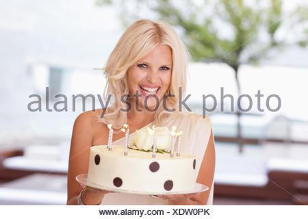 Porträt der Frau hält Geburtstagstorte - Stockfoto