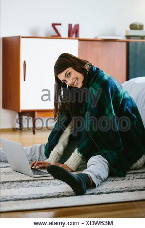 Junge Frau trägt Decke mit laptop - Stockfoto