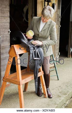 Eine Frau, Reinigung und Vorbereitung Tack und Sattel im Hof des einen Reitstall.