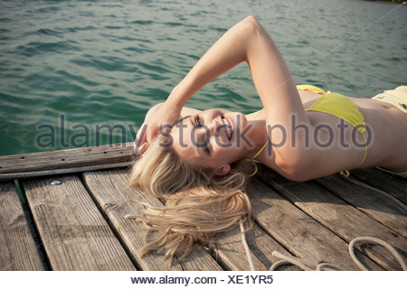 Porträt der jungen Frau, die auf See Pier liegt - Stockfoto