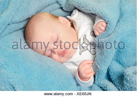 Entzückende kleine Baby friedlich schlafend auf einer Decke - Stockfoto
