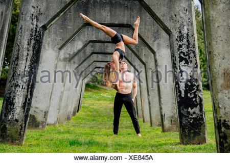 Junge Frau balancieren auf Mannhände praktizieren Yoga unter Betonbrücke - Stockfoto
