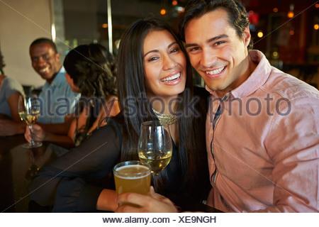 Paar genießt Drink an der Bar mit Freunden - Stockfoto
