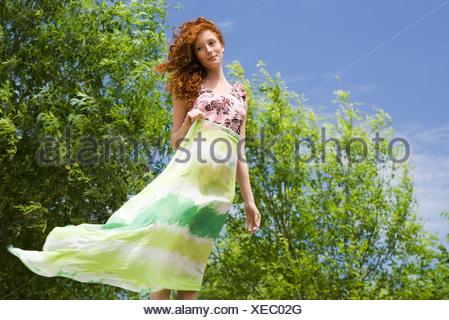 Junge Frau im Freien stehen, halten Schal im wind - Stockfoto