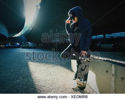 Junger Mann Stehen Auf Einem Bein Mit Skateboard Unter Brücke   Stockfoto