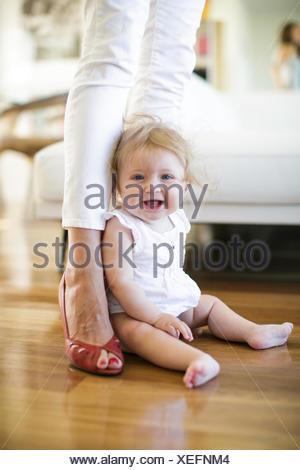 Porträt von Babymädchen sitzen auf dem Boden zwischen den Beinen Mutter - Stockfoto