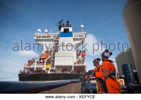 Arbeitnehmer auf Schlepper in Seil ziehen - Stockfoto