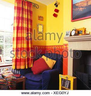 https://l450v.alamy.com/450vde/xeg0yj/blaue-sessel-in-der-ecke-des-hellen-gelben-wohnzimmer-mit-rot-gelb-vorhange-gepruft-und-bemalt-rot-dado-xeg0yj.jpg