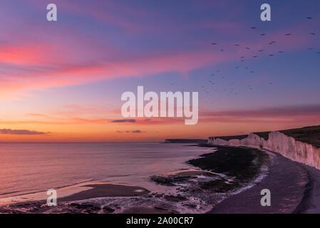 Puesta de sol sobre los Birling Gap y Las Siete Hermanas con aves volando por encima