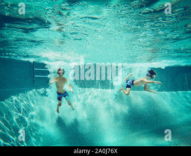 Imagen Submarina de dos chicos saltando a una piscina juntos.