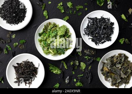 Diversas algas secas, verduras de mar, tomada desde arriba sobre un fondo negro