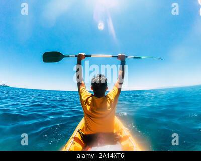 Vista trasera del hombre turistas abandonan las armas disfrutando de la excursión en kayak en el océano azul del agua - Concepto de felicidad para viajes y actividades recreativas o