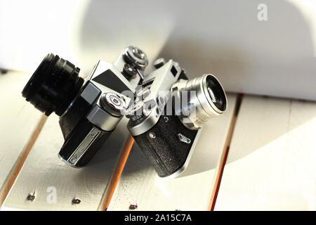 Dos negras de la vieja escuela de cine vintage cámaras fotográficas sobre tablones de madera blanca interior, iluminado por el sol,