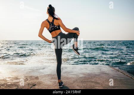 Vista trasera de una mujer estirando su pierna en un muelle