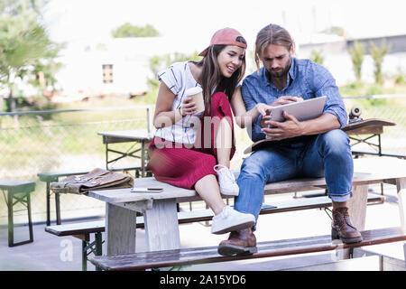 Pareja joven sentado en la mesa en un jardín de cerveza con tablet Foto de stock