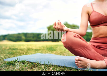 Close-up de mujer practicando yoga en el parque