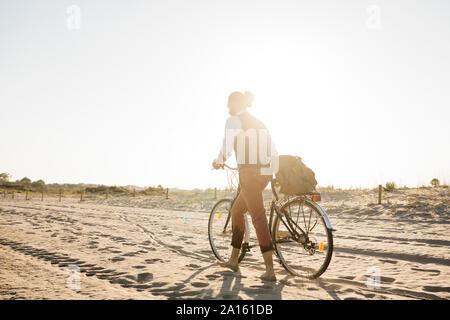 El hombre bien vestido caminando con su bicicleta en una playa en el atardecer.