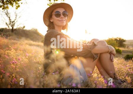 Mujer joven llevar sombrero para el sol y sentarse en pradera al atardecer
