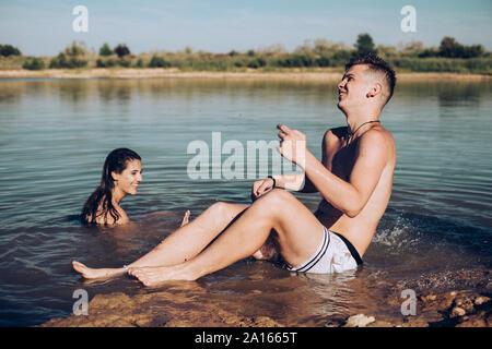 Pareja joven divirtiéndose en un lago Foto de stock