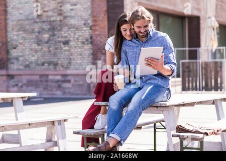 Pareja joven sentado en la mesa en un jardín de cerveza mirando tablet Foto de stock