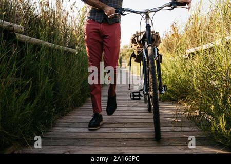 El hombre bien vestido caminando con su bicicleta en una pasarela de madera en el campo después del trabajo