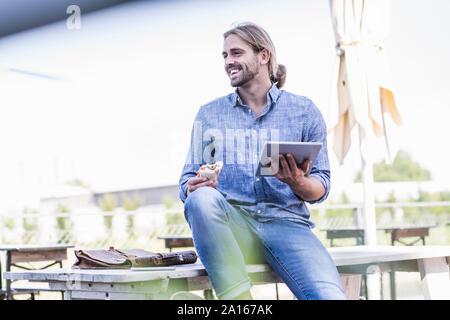 Hombre joven sentado en la mesa en un jardín de cerveza con tablet y sándwiches. Foto de stock