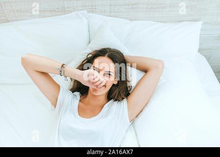 Retrato de mujer joven feliz tumbado en la cama en casa Foto de stock
