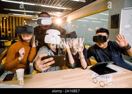 Cinco jóvenes personas divertidas sentado a la mesa en frente uno del otro, utilizando gafas de realidad virtual, divertirse y gesticula. Concepto gafas VR