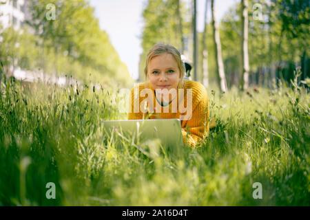 Retrato de mujer sonriente tumbado en una pradera utilización portátil
