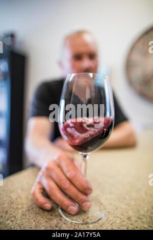 Hombre remolinos de un vaso de vino tinto durante una cata de vinos.
