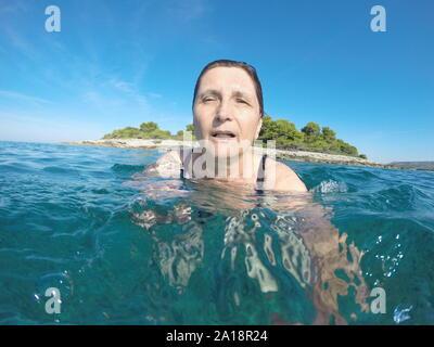 Mujer madura, nadando en el azul claro del mar Adriático