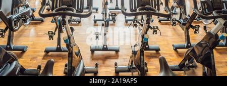 Aeróbic spinning bicicletas de ejercicio gimnasio con muchos en una fila de Banner, formato largo Foto de stock