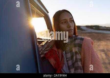Mujer joven recostada sobre una camioneta pick-up durante una parada en un viaje por carretera
