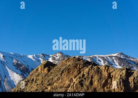 Vista escena de escaladores alcanzando el pico de la montaña contra montañas nevadas de Los Andes en la Patagonia, Esquel, Argentina