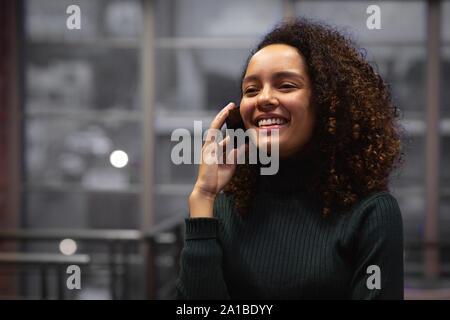 Las hembras jóvenes creativos de negocios utilizando el smartphone